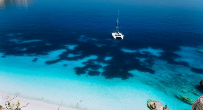 White catamaran yacht drift on clear azure water surface in calm blue lagoon with transparent water and dark pattern on bottom.